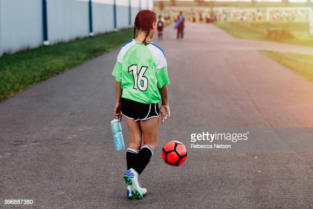 girl dribbling soccer ball to her field to begin play - チームジャージ ストックフォトと画像