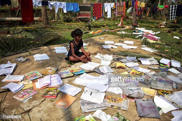 TOPSHOT A girl dries her books in Puri in the eastern Indian state of Odisha on May 9 2019 after the passage of cyclone Fani At least 42 people lost...