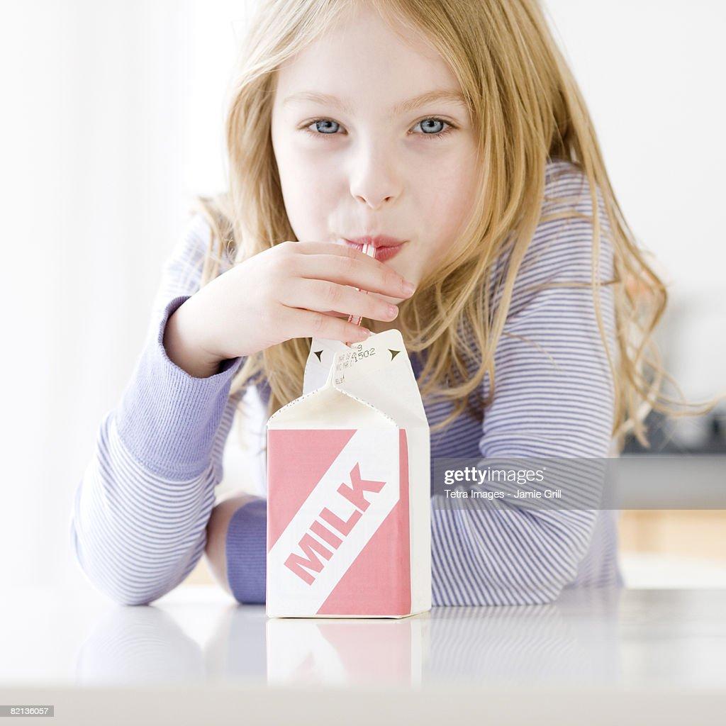 Girl drinking carton of milk : Stock Photo