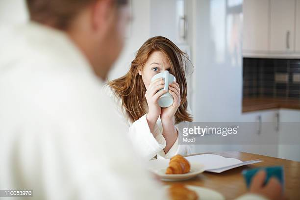 Girl drinking coffee in kitchen
