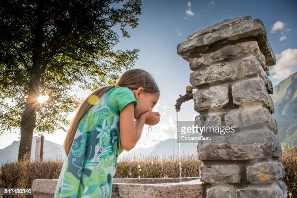 Mädchen trinken frische Wasser aus der Dorf-Quelle