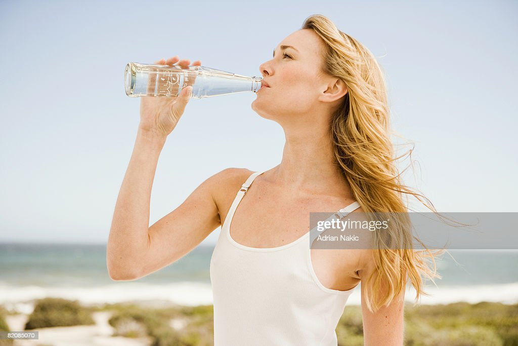 girl drinking from glass bottle at beach. : Stock Photo