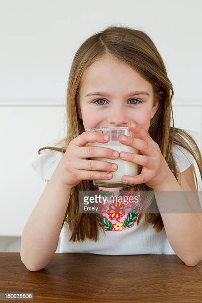 Girl drinking glass of milk at table