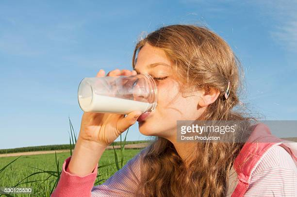 Girl (12-13) drinking glass of milk outdoors, eyes closed, portrait