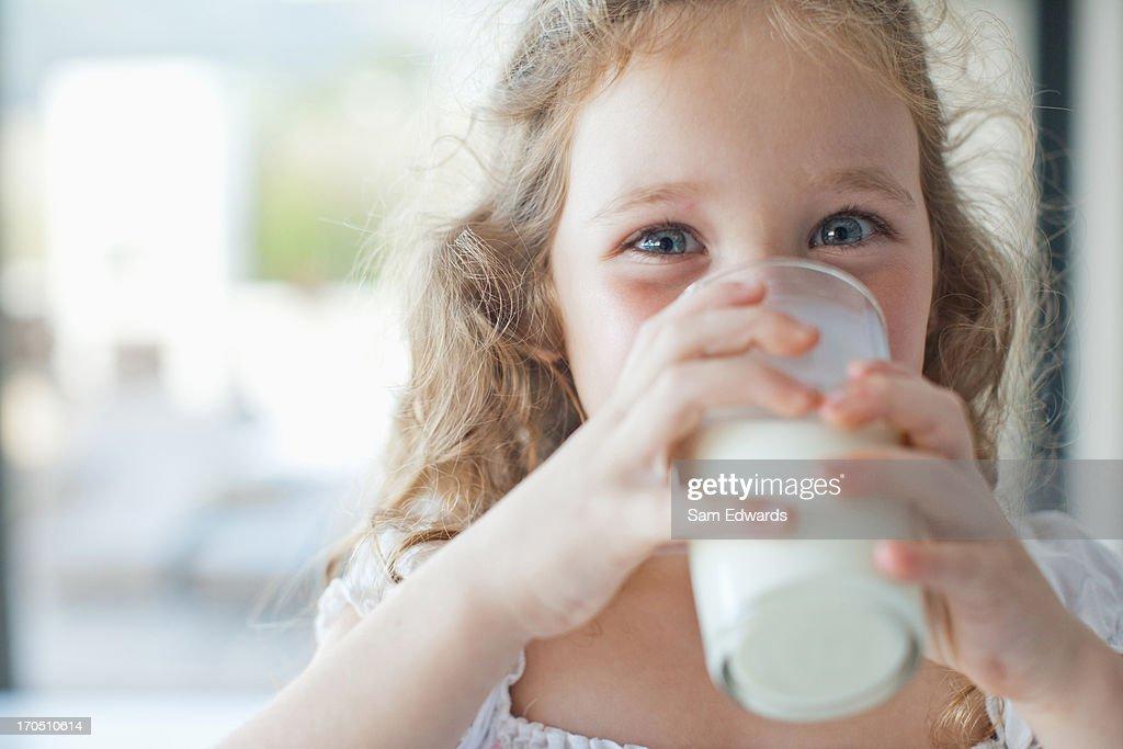 Bambina bere un bicchiere di latte : Foto stock