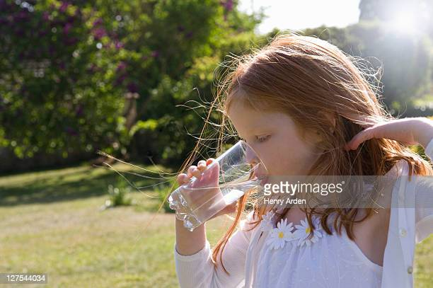 Girl drinking glass of water in backyard