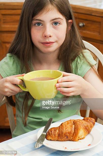 Girl drinking hot chocolate with croissant