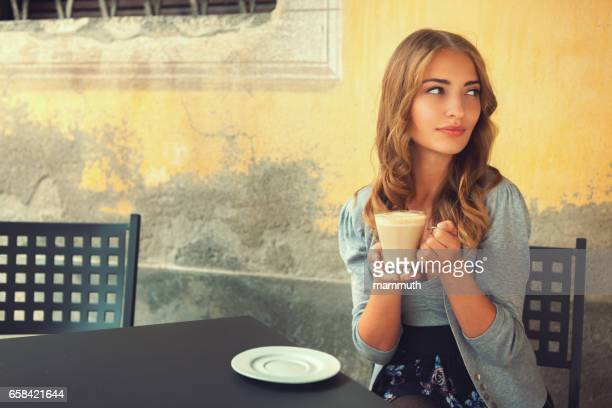 Girl drinking latte in an italian cafe