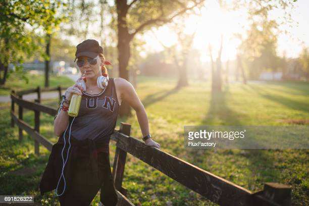 a girl drinking lemonade while resting after jogging - mp3 juices stock photos and pictures