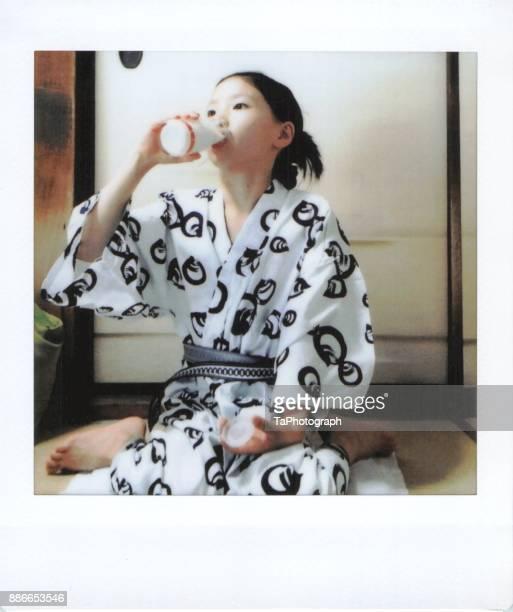 girl drinking milk in a kimono - 銭湯 ストックフォトと画像