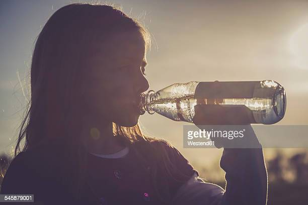 girl drinking water out of a water bottle at backlight - erfrischung stock-fotos und bilder