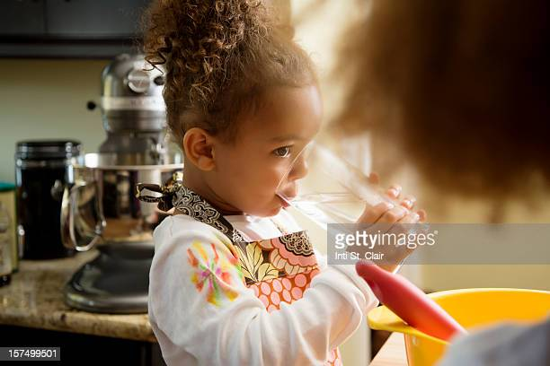 Girl drinking water while baking in the kitchen