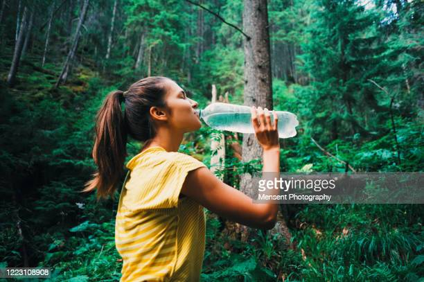 girl drinking water while out hiking - thirsty stock pictures, royalty-free photos & images