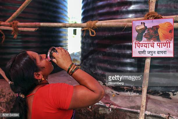 A girl drinks water from a cup while standing next to water tanks inside a temporary suburban camp set up by local political party Shiv Sena for the...