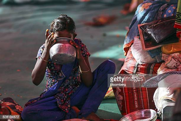 A girl drinks water from a vessel inside a temporary suburban camp set up by local political party Shiv Sena for the rural poor traveling to Mumbai...