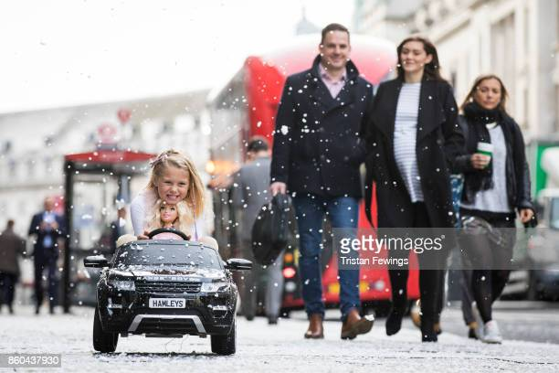 A girl drives a Range Rover Evoque Rideon electric car on Regents Street as Hamley's announce it's top ten toys for Christmas at Hamleys on October...