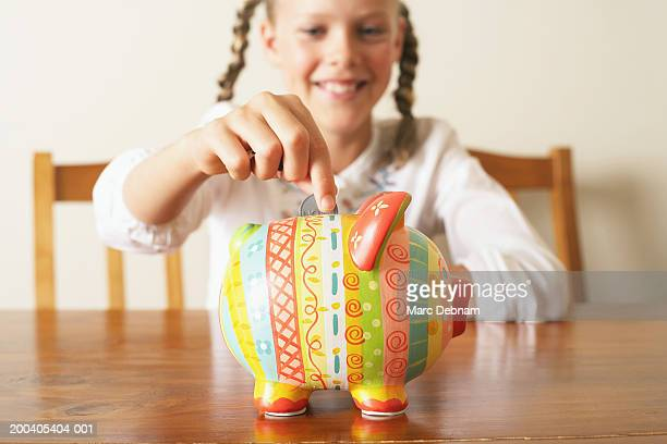 Girl (10-12) dropping coin into piggy bank (focus on piggy bank)