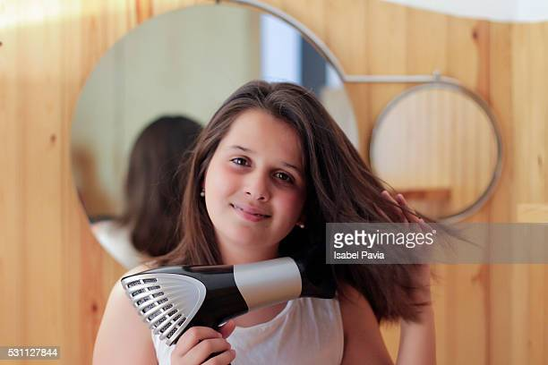 Girl drying her hair in domestic bathroom