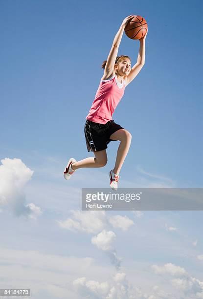 Girl dunking basketball, airborne