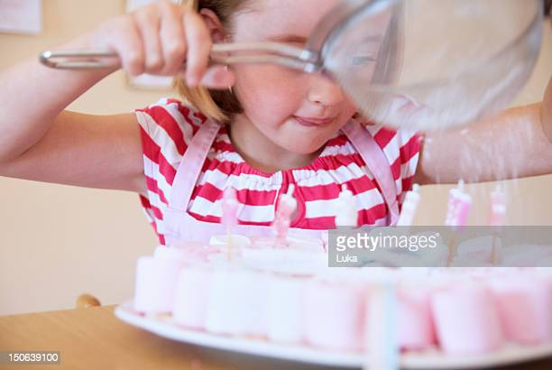 Girl dusting candies with sugar