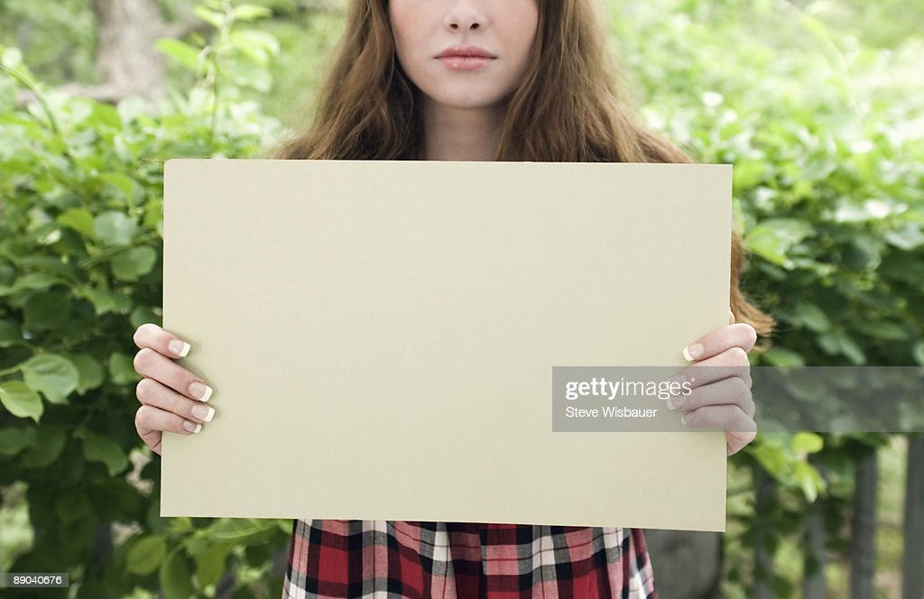 Girl early 20's holding blank sign expressionless  : Stockfoto