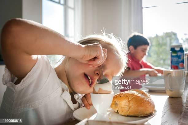 girl eating a boiled egg at dining table - frühstück stock-fotos und bilder