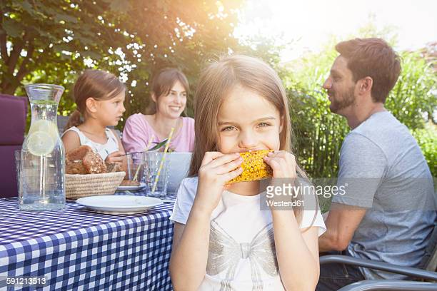 Girl eating a corn cob on a family barbecue in garden