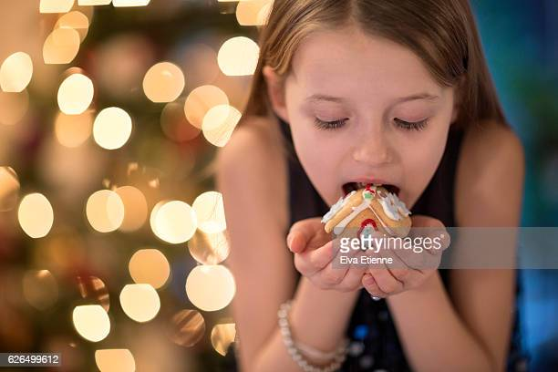 Girl (9-10) eating a gingerbread house