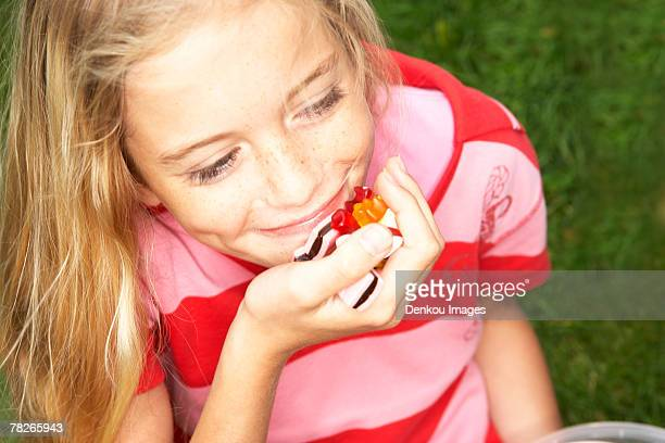 A girl eating a handful of candy.