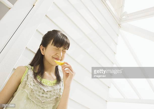 Girl eating a lemon outside