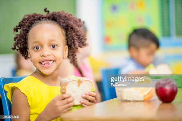 girl eating a sanndwich - cracker snack stock photos and pictures