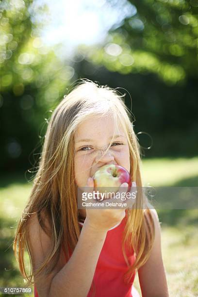 A girl eating an apple in a garden