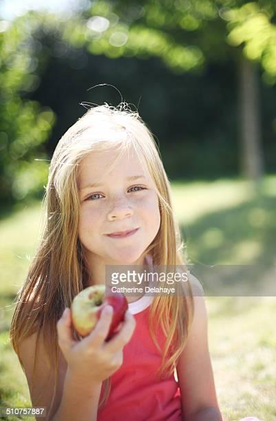 A girl eating an apple in a garden