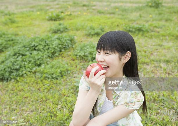 Girl eating an apple in the field