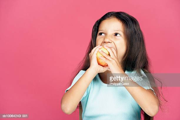 Girl (4-5) eating apple and looking up