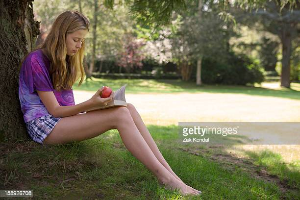 Girl eating apple and reading in park