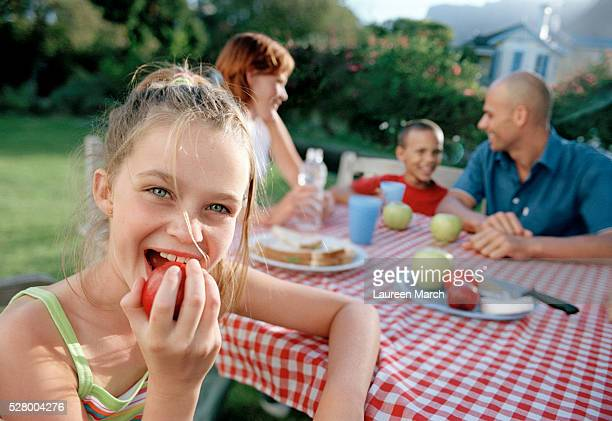 Girl Eating Apple at Table