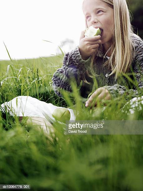 Girl (8-9) eating apple in meadow, differential focus
