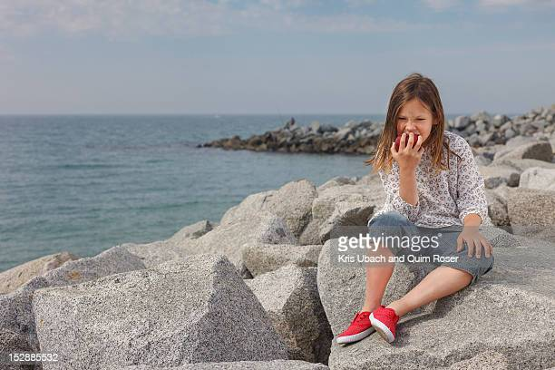 Girl eating apple on rocky beach
