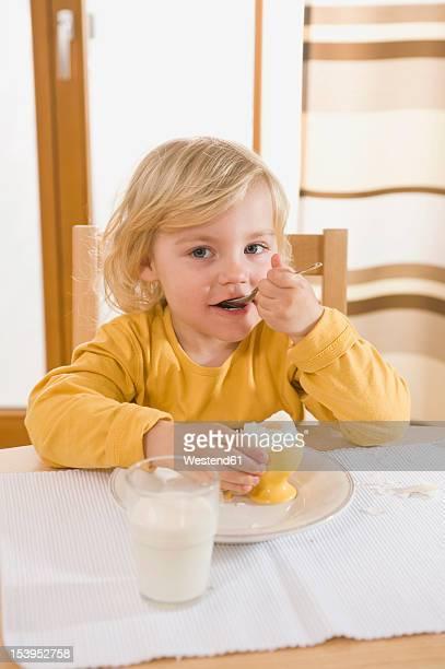 Girl eating boiled egg in breakfast, eating egg