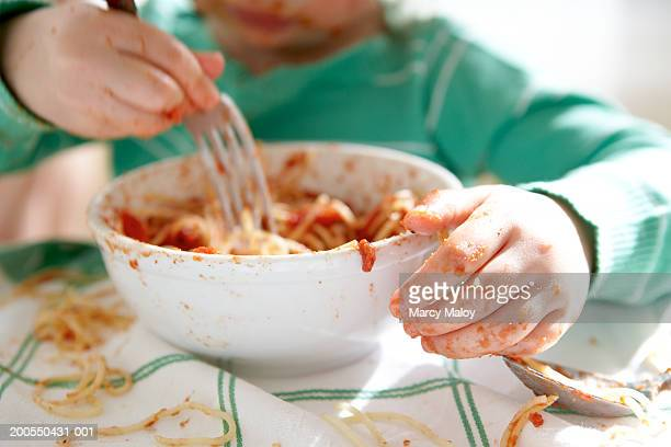 Girl (2-4) eating bowl of spaghetti, mid section (focus on hand)