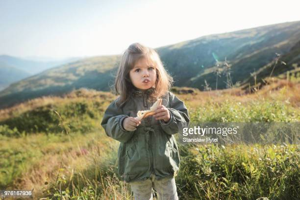 Girl eating bread in mountains