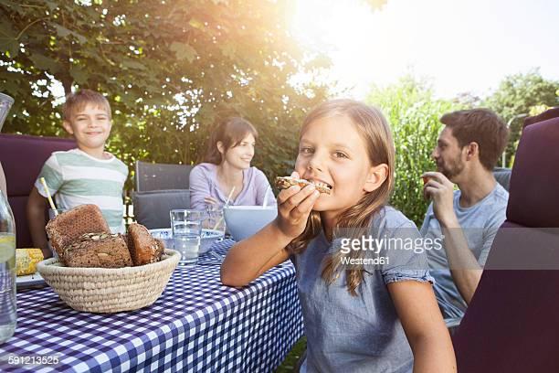 girl eating bread with family at garden table - essen mund benutzen stock-fotos und bilder