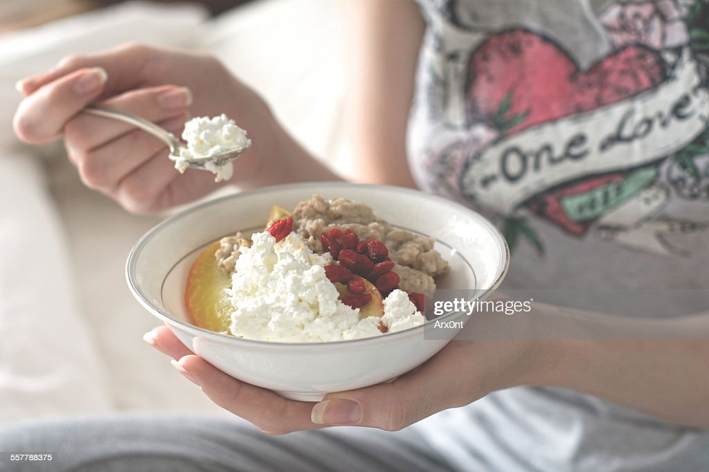 Girl eating breakfast : Stock Photo