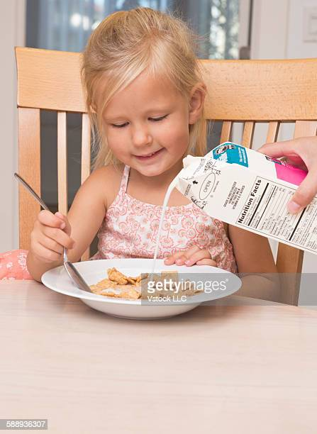 girl (2-3) eating breakfast - milk carton stock photos and pictures