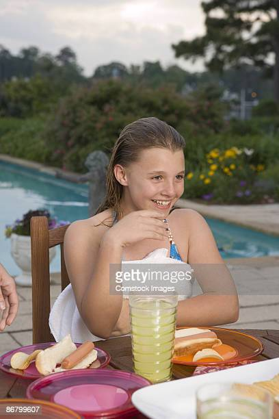 Girl eating by swimming pool