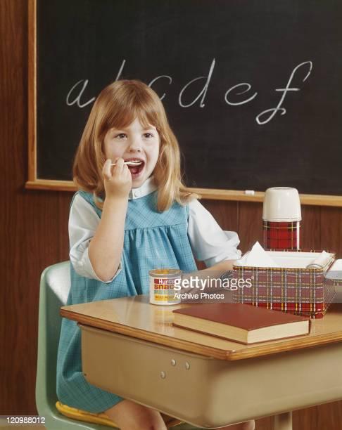 Girl eating canned food sitting beside blackboard