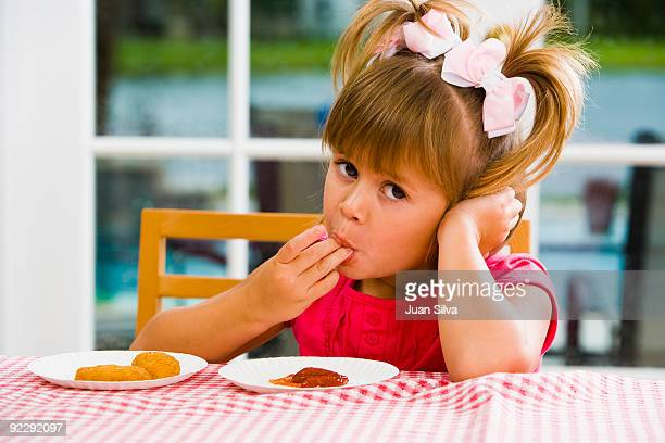 Girl eating chicken nuggets with ketchup on table