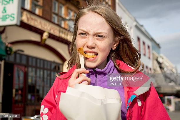 Girl (8-9) eating chips, seaside