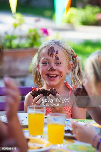 Girl eating chocolate cake, face covered in icing